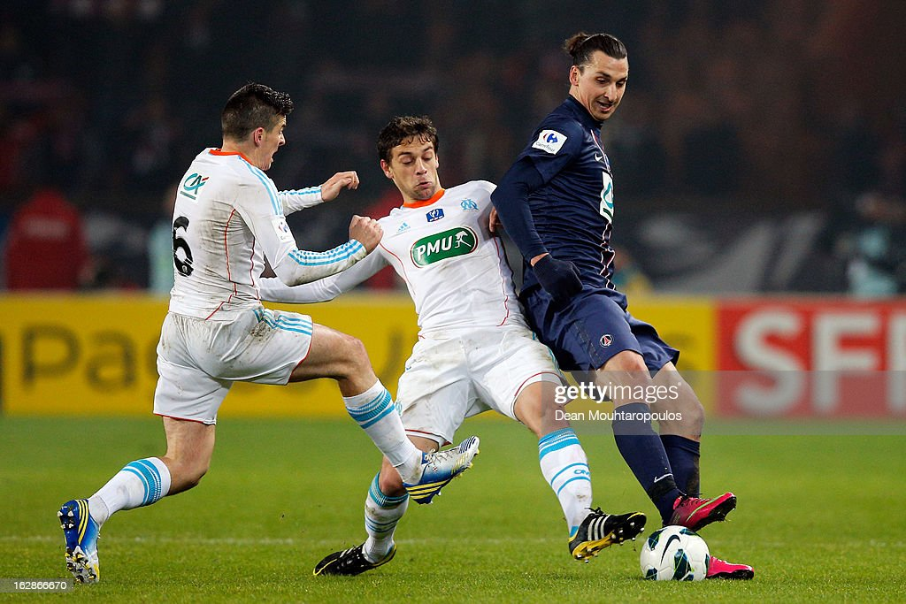 Zlatan Ibrahimovic of PSG beats Michel Lucas Mendes and Joey Barton of Marseille during the French Cup match between Paris Saint-Germain FC and Marseille Olympic OM at Parc des Princes on February 27, 2013 in Paris, France.