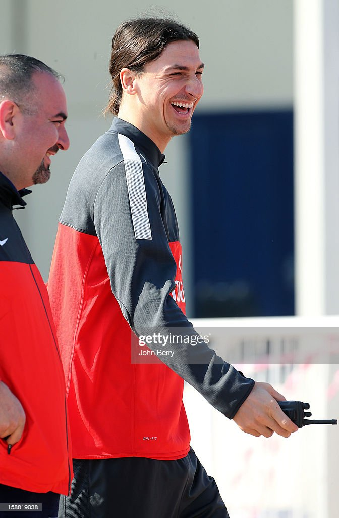 Zlatan Ibrahimovic of PSG gives funny instructions to all the security guards after borrowing a walkie-talkie from a bodyguard, on his way to the Paris Saint Germain training session held at the Aspire Academy for Sports Excellence on December 30, 2012 in Doha, Qatar.