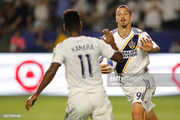 Zlatan Ibrahimovic of the Los Angeles Galaxy prepares to highfive teammate Ola Kamara after a goal at StubHub Center on July 29 2018 in Carson...