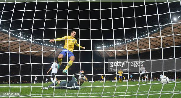 Zlatan Ibrahiomovic of Sweden jumps over Manuel Neuer of Germany as he scores his goal during the FIFA 2014 World Cup qualifier group C match between...