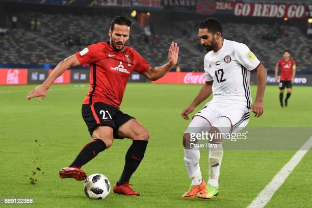 Zlatan Ljubijankic of Urawa Red Diamonds and Salim Rashid compete for the ball during the FIFA Club World Cup match between Al Jazira and Urawa Red...