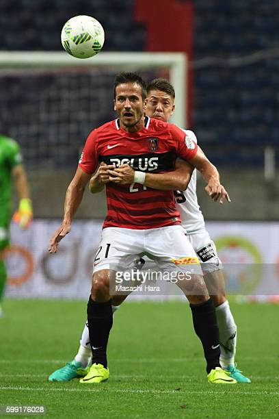 Zlatan of Urawa Red Diamonds and Masahiko Inoha of Vissel Kobe compete for the ball during the JLeague Levain Cup match between Urawa Red Diamonds...