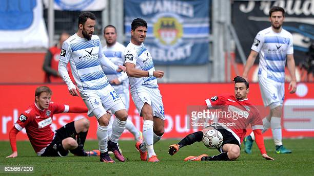 Zlatko Janjic and Baris Oezbek of Duisburg vies with Rico Preissinger of Aalen during the 3 Liga match between MSV Duisburg and VfR Aalen at...
