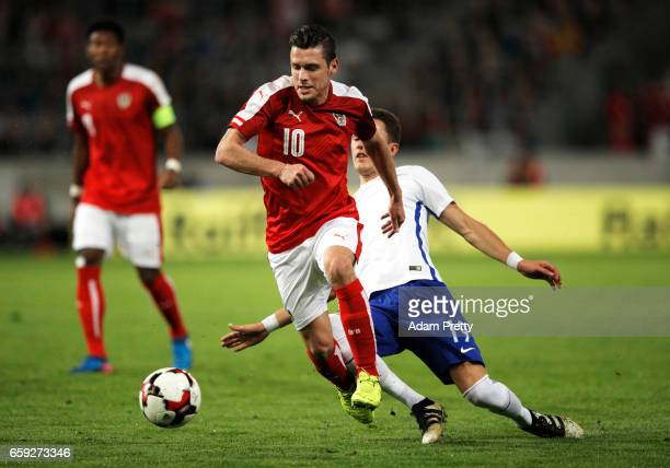 Zlatko Junuzovic of Austria is tackeld by Thomas Lam of Finland during the Austria v Finland International Friendly match at Tivoli Stadium on March...
