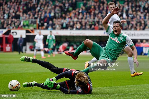 Zlatko Junuzovic of Werder Bremen is challenged by Loris Karius of 1 FSV Mainz 05 during the Bundesliga match between Werder Bremen and 1 FSV Mainz...