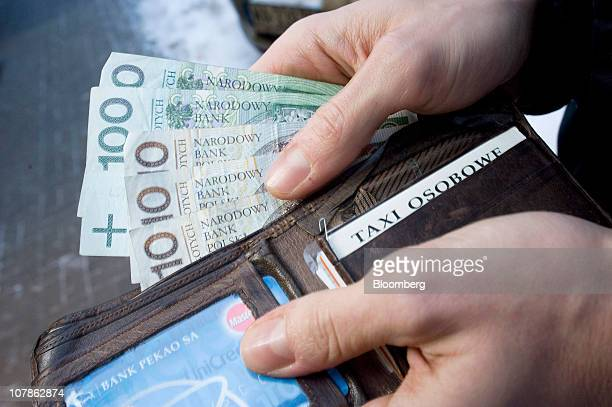 Zloty notes are removed from a wallet in an arranged photograph in Warsaw Poland on Friday Dec 312010 Poland's central bank may start increasing...