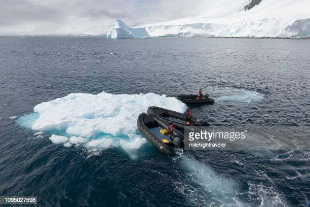 Zodiac expedition guides push iceberg Damoy Point Wiencke Island Antarctic Peninsula Antarctica