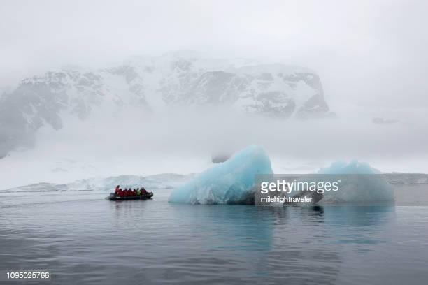 Zodiac motorboat carries travelers Danco Island glacier iceberg Antarctica Gerlache Strait Antarctica