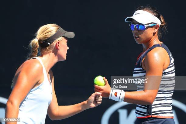 Zoe Hives of Australia and Alison Bai of Australia talk tactics in their first round women's doubles match against Madison Brengle of the United...