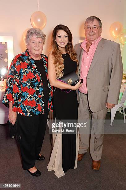 Zoe Sugg poses with her Nan and Grandad at the launch of her debut beauty collection at 41 Portland Place on September 25 2014 in London England