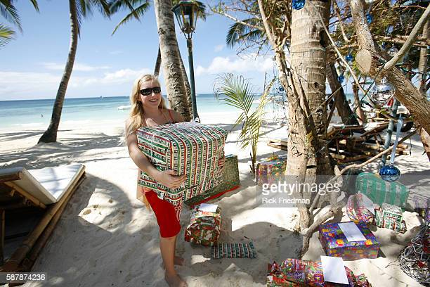 Zoe Vogel of Basel Switzerland gets ready for Christmas by placing gifts under a palm treeturnedChristmas tree on the beach