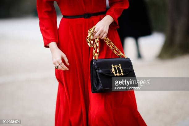Zoey Deutch wears a Dior bag and a red dress, outside Dior, during Paris Fashion Week Womenswear Fall/Winter 2018/2019, on February 27, 2018 in...