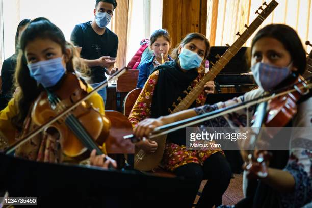 Zohra trumpet player, center, plays her instrument during rehearsal for Zohra orchestra at Afghanistan National Institute of Music, in Kabul,...