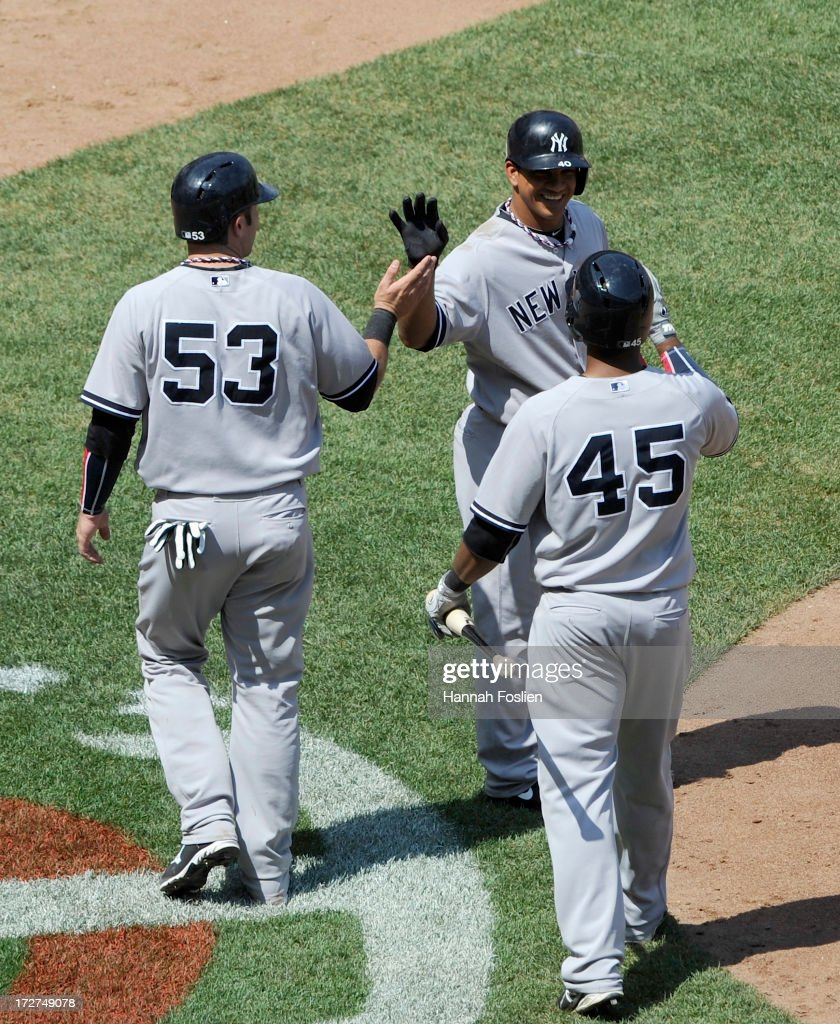 Zoilo Almonte #45 of the New York Yankees congratulates teammates Austin Romine #53 and Alberto Gonzalez #40 on scoring against the Minnesota Twins during the sixth inning of the game on July 4, 2013 at Target Field in Minneapolis, Minnesota. The Yankees defeated the Twins 9-5.