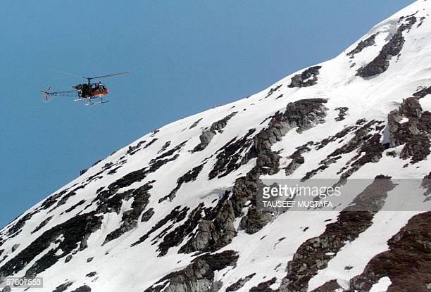 An Indian army helicopter flies over the Zojila pass on the SrinagarLeh National Highway after the road was opened after months of being closed for...