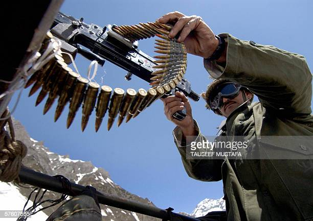 An Indian soldier checks his gun as he stands guard on the Zojila pass on the SrinagarLeh National Highway after the road was opened after months of...