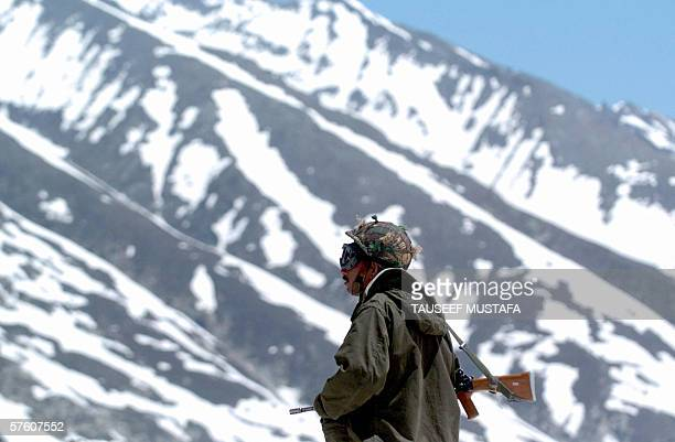 An Indian soldier stands guard on the Zojila pass on the SrinagarLeh National Highway after the road was opened after months of being closed for the...