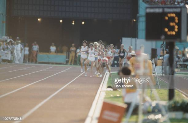 Zola Budd of Great Britain leads as Mary Decker of the United States trips and crashes out of the race during competition in the final of the Woman's...