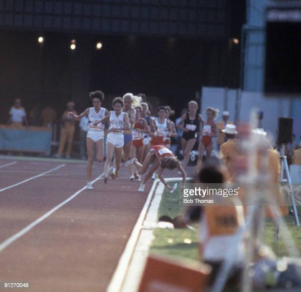 Zola Budd of Great Britain leads as Mary Decker of the United States trips and crashes out of the race after clashing with Budd during competition in...