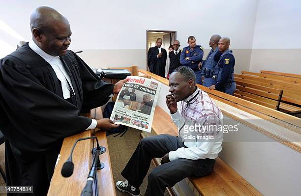 Zola Majavu shows his client Chris Mahlangu the front page photo of The Herald newspaper inside Ventersdorp magistrates court on April 12 2012 in...