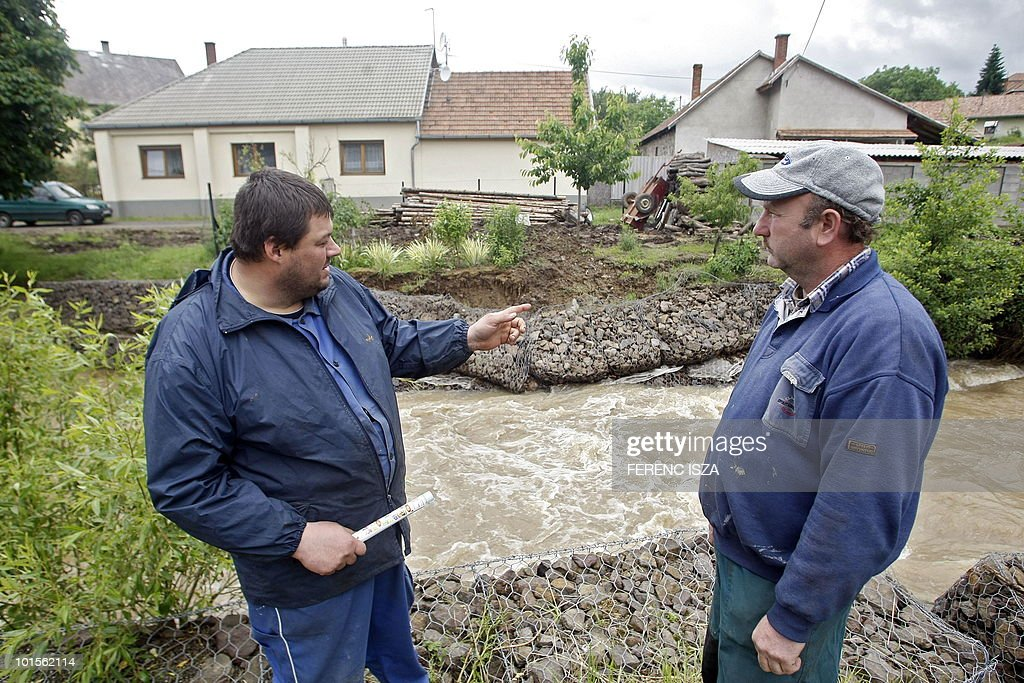 Zoltan and Janos look at the 'Kovecses' creek near their house before they are evacuated from the Hungarian city Paszto 80 km north-east from Budapest on June 2, 2010. A level-three alert, the highest, has been declared because of the high water level..