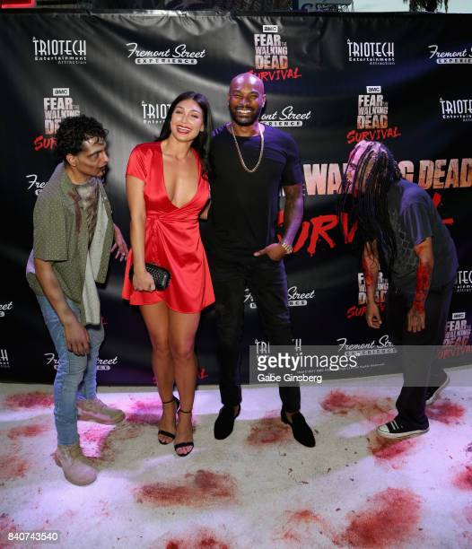 Zombie characters photobomb actor/model Tyson Beckford and a guest as they attend the Fear the Walking Dead Survival attraction grand opening at the...