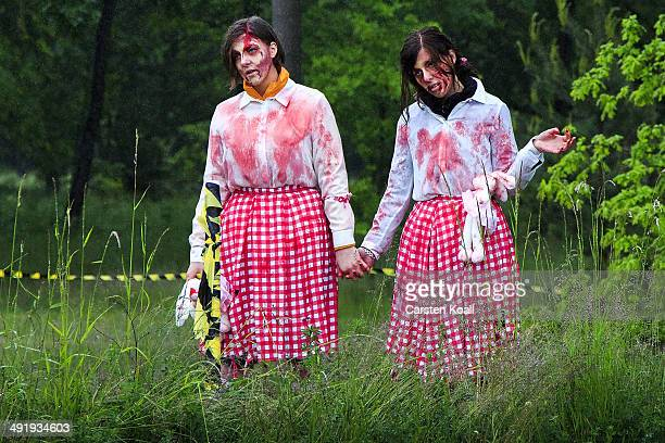 Zombie clowns wait for the runners as they take part in the 'Zombie Run' on May 18 2014 in Berlin Germany The race sees participants attempt to...
