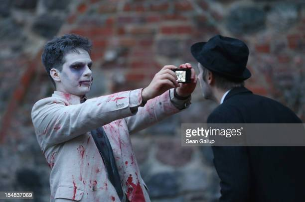 Zombie enthiusiasts gather before setting out on a 'Zombie Walk' in the city center on October 27 2012 in Berlin Germany Approximately 150 zombies...