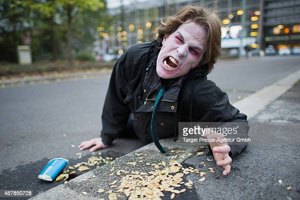 A zombie enthusiast crawls over the Alexanderplatz as part of a flashmob on October 25 2014 in Berlin Germany Over 150 participants dressed as...