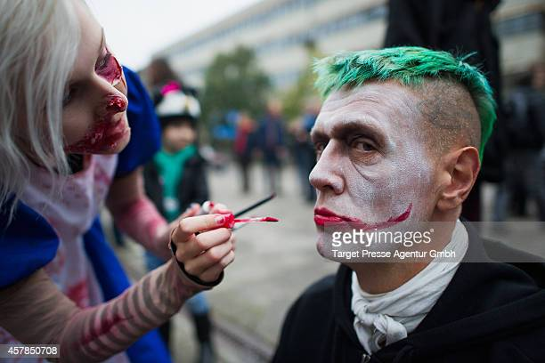 A zombie enthusiast is getting a fresh make up as part of a flashmob on October 25 2014 in Berlin Germany Over 150 participants dressed as zombies...