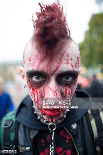 A zombie enthusiast walks over the Alexanderplatz as part of a flashmob on October 25 2014 in Berlin Germany Over 150 participants dressed as zombies...