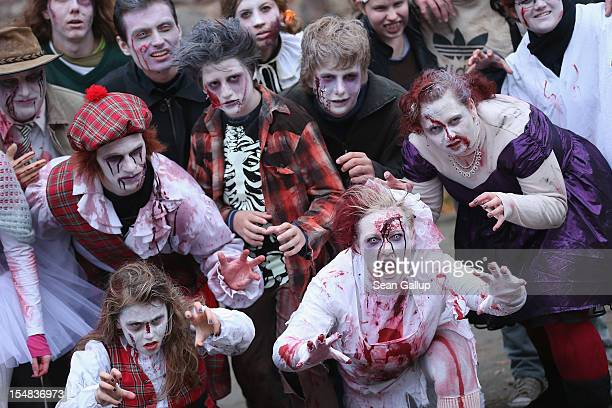 Zombie enthusiasts practice being scary before setting out on a 'Zombie Walk' in the city center on October 27 2012 in Berlin Germany Approximately...