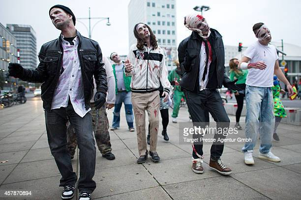 Zombie enthusiasts walk over the Alexanderplatz as part of a flashmob on October 25 2014 in Berlin Germany Over 150 participants dressed as zombies...