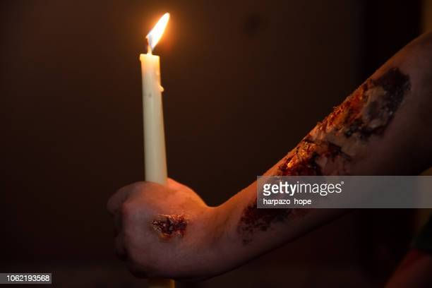 zombie hand with rotting flesh makeup holding a candle at night. - candle of hope imagens e fotografias de stock