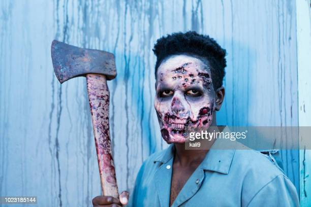 zombie in haunted house holding axe - zombie face stock photos and pictures