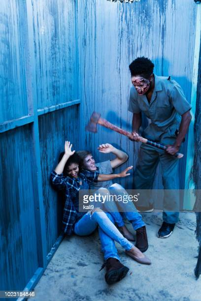zombie in haunted house standing over victims with axe - murder victim stock pictures, royalty-free photos & images