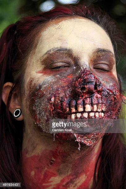 A 'zombie' prepares for the runners as they take part in the 'Zombie Run' on May 18 2014 in Berlin Germany The race sees participants attempt to...