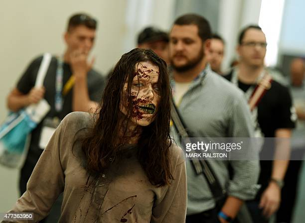 A zombie promoting The Walking Dead game walks amongst gamers at the opening day of the Electronic Entertainment Expo known as E3 at the Convention...