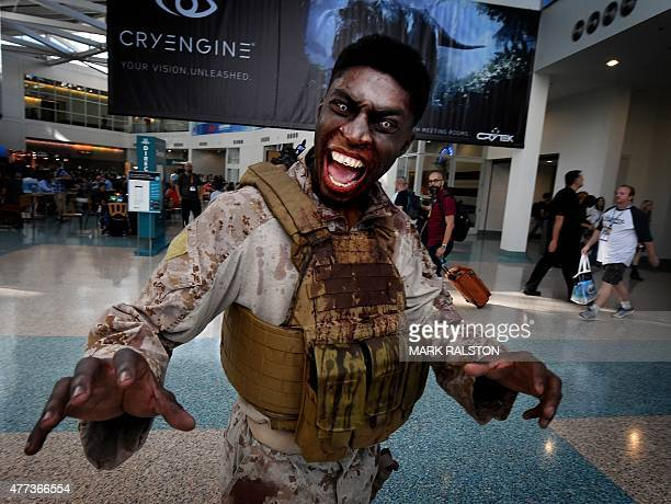 A zombie promoting 'The Walking Dead' game walks amongst gamers at the opening day of the Electronic Entertainment Expo known as E3 at the Convention...