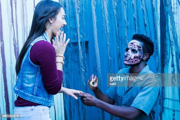 zombie proposing to surprised girl with toy ring - black women engagement rings stock pictures, royalty-free photos & images