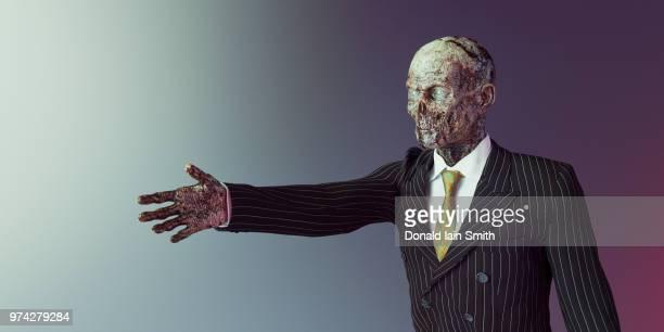 Zombie: surreal studio portrait of a zombie businessman in suit and tie extending hand