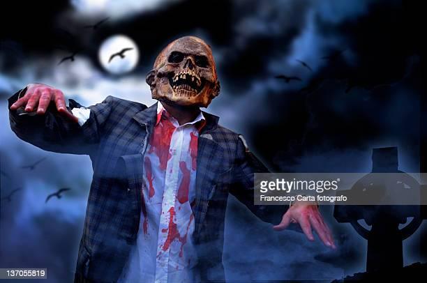 Zombie walk at night cemetery