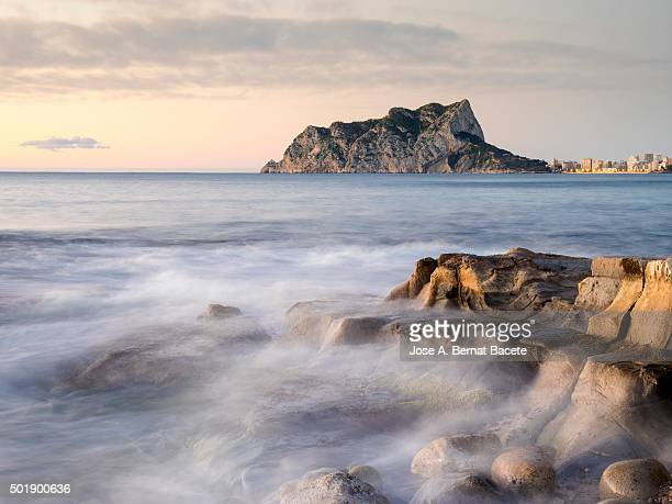 Zone of coast with rocks and with the sea in movement one morning to the dawn in a cala of Calpe's city.
