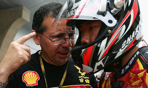 Zongshen Motorcycle Racing Team Director Michel Marqueton gives instructions to Li Zhengpeng ahead of the 250cc free practice session at Shanghai International ...