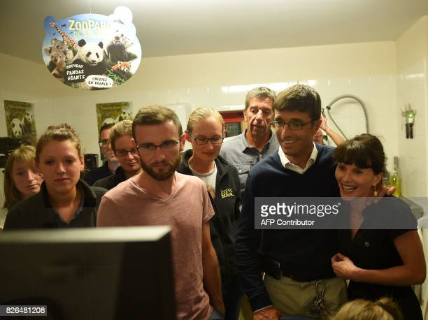 Zoo Director Rodolphe Delord flanked by his wife French host tv and medecin Michel Cymes and team look at the female panda Huan Huan on screen in...