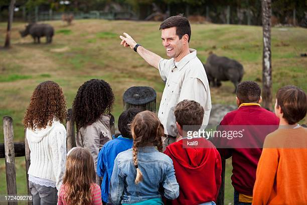 zoo keeper with group of children at rhino exhibit - zoo keeper stock pictures, royalty-free photos & images