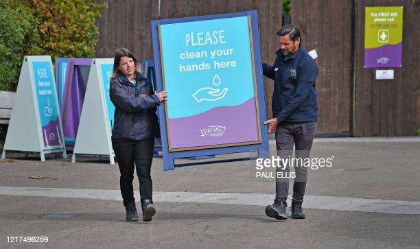 Zoo personnel move coronavirus health warning signs at Chester Zoo in Chester north west England on June 4 2020 Following the lockdown due to the...