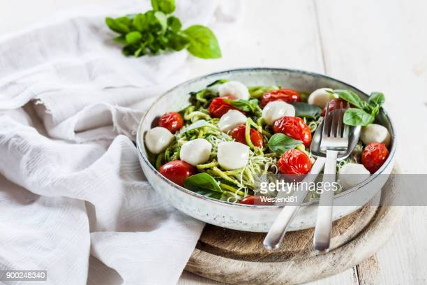 zoodles caprese, spiralized zucchini, glass noodles, pesto, plum tomatoe, mozarella balls - dish towel stock pictures, royalty-free photos & images