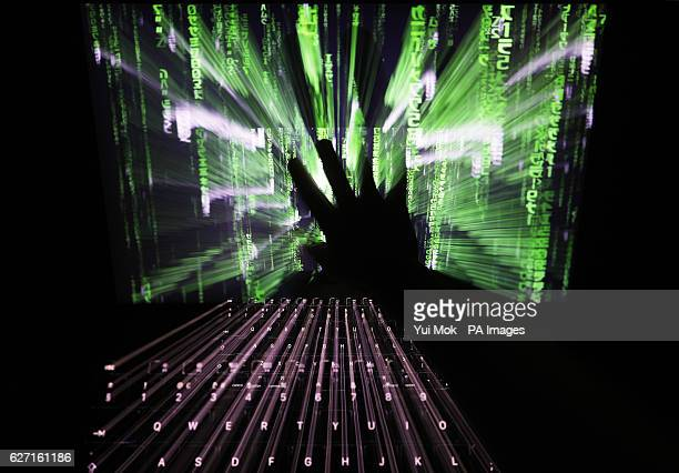 A zoom burst photo of a user touching the screen of a laptop displaying a 'Matrix'style screensaver in London