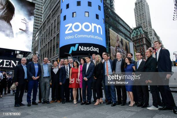 Zoom founder Eric Yuan poses with members of his company in front of the Nasdaq building as the screen shows the logo of the video-conferencing...
